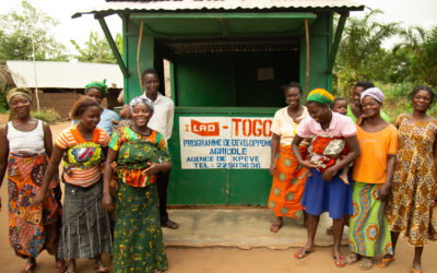 """Happy Togolese men and women stand in front of a sign which reads """"ILAD Togo..."""""""