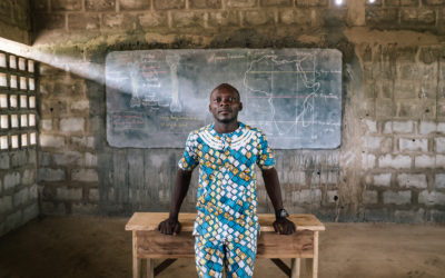 Young Togolese Secondary Education Teacher standing in front of a desk and chalk board, featuring a map of Africa