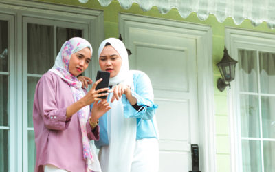 Two young Filipino women wearing head scarves looking at a cellphone together, one pointing out something to the other. They are on the front porch of a house.